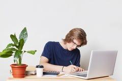 De ernstige mens met in kapsel, draagt vrijetijdskleding, zit op het werkplaats, bestudeert documenten werkt aan laptop computer  royalty-vrije stock afbeeldingen