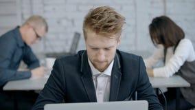 De ernstige mens werkt met computer op het kantoor stock videobeelden