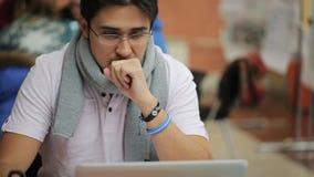 De ernstige mens zit in bureau en werkt aan laptop stock footage