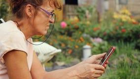 De ernstige mooie rijpe vrouw in oud in glazen zit in de tuin op het schommelingsgebruik een mobiele telefoon stock foto