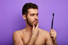 De ernstige nadenkende jonge mens houdt tandenborstel en het bekijken het royalty-vrije stock foto