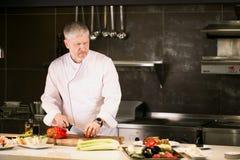 De ernstige oude gebaarde chef-kok in witte speciale clothers maakt snacks stock afbeeldingen