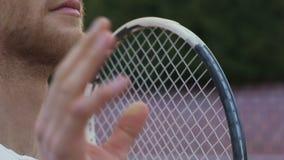 De ernstige sportman werpt en vangt tennisbal, blijft zeker van overwinning stock video