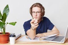 De ernstige strikte mannelijke werkgever zit bij bureaubinnenland, richt met wijsvinger op u, waarschuwt over straf Knappe jonge  stock foto