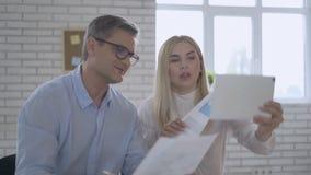 De ernstige succesvolle zakenlieden tonen een grafiek met een rapport Online conferentie over de tablet modern technologieconcept stock video