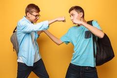 De ernstige tegenstanders, twee tieners, kerels tonen vuist, klaar voor slag, hebben strikt gelaatsuitdrukking, op geel achtergro stock fotografie
