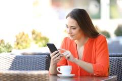 De ernstige vrouw doorbladert een smartphone in een koffiewinkel stock foto's