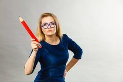 De ernstige vrouw houdt groot potlood in hand royalty-vrije stock foto's