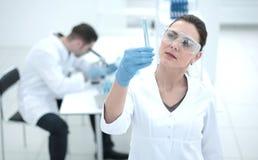 De ernstige vrouwelijke wetenschapper bekijkt de buis met de resultaten van de analyse royalty-vrije stock fotografie