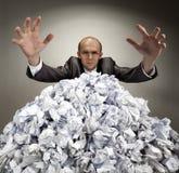 De ernstige zakenman bereikt uit van documenten stock foto's