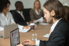 De ernstige zakenman die aan laptop bij divers werken groepeert me online stock afbeelding