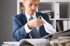 De ernstige zakenman in het bureau onderzoekt documenten Royalty-vrije Stock Foto