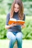 De ernstige zitting van het studentenmeisje op stapel van boeken Stock Fotografie
