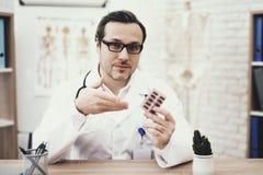 De ervaren arts met stethoscoop in medische peignoir houdt blaarpak tabletten stock foto