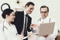 De ervaren arts toont op laptop resultaten van algemeen medisch onderzoek van succesvolle zakenman stock afbeeldingen