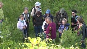 De ervaren gids vertelt toeristenmensen over zeldzame species van installaties en bloemen stock video