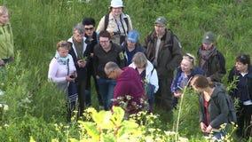 De ervaren gids vertelt toeristenmensen over zeldzame species van installaties en bloemen stock footage
