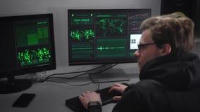 De ervaren hakker voert cyber aanvallen op belangrijke bedrijvenserver uit om geld van hun rekeningen te stelen Mens die met stock videobeelden