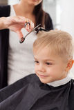 De ervaren jonge vrouwelijke kapper dient kind stock afbeeldingen