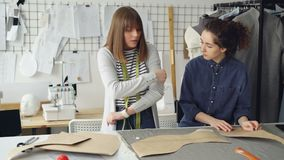 De ervaren kleermaker onderwijst jonge vrouw om kokers te naaien Zij spreekt, gesturing, toont textiel en kleedt zich stock footage