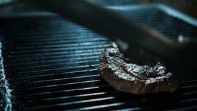 De ervaren kok braadt rundvleesplak bij de grill in keuken van restaurant stock video