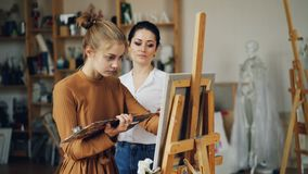 De ervaren kunstleraar werkt met mooi meisje talanted student het schilderen beeld en het spreken delend ervaring stock video