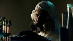 De ervaren midden oude wetenschapper in ademhalingsapparaat maakt een experiment met spuit of injecteur De chemicus vindt gewijzi stock video