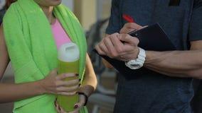 De ervaren trainer schrijft en spreekt aan vrouw in sportclub stock footage