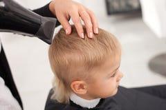 De ervaren vrouwelijke kapper maakt kapsel aan stock foto's