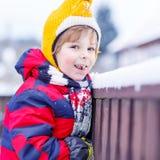 De etende en proevende sneeuw van weinig jong geitjejongen, in openlucht op koude dag Royalty-vrije Stock Afbeeldingen