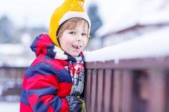 De etende en proevende sneeuw van weinig jong geitjejongen, in openlucht op koude dag Royalty-vrije Stock Foto's