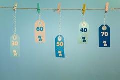 De etiketten hangen op een kabel in bijlage met wasknijpers De waarden van de korting worden geschreven op hen, vijftig, dertig,  Stock Afbeelding