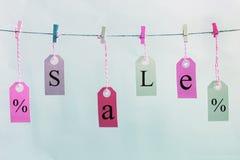 De etiketten hangen op de kabel met gekleurde wasknijpers Zij zijn inschrijvingsverkoop en een percententeken stock foto