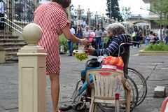De etnische oude vrouwenzitting op rolstoel ontvangt Kerstmisaalmoes van vrouw bij oude kerkyard royalty-vrije stock fotografie