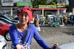 De etnische rijpe vrouw glimlacht aangezien zij voor aalmoes bij oude kerkyard bedelt Sluit omhoog royalty-vrije stock afbeelding