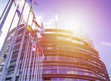 De EU-Parlementsgebouw met vlaggen in zonlicht Stock Foto's