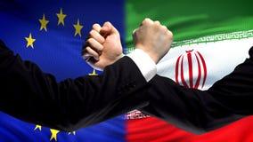 De EU versus de confrontatie van Iran, het meningsverschil van landen, vuisten op vlagachtergrond stock afbeeldingen