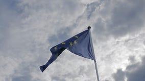 De EU-vlag die in de wind tegen een blauwe hemel golven Het concept patriottisme Langzame Motie stock videobeelden
