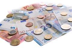 De euro bankbiljetten en de muntstukken sluiten omhoog op witte achtergrond Royalty-vrije Stock Foto's