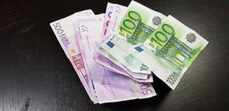 De euro bankbiljetten van 100 en 500 leggen op de lijst stock foto's