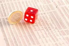 De euro muntstukken en het rood dobbelen op financiële krant Stock Afbeelding