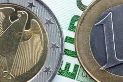 De euro muntstukken op euro bankbiljet sluiten omhoog Stock Foto's
