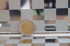 De euro muntstukken in spiegel denken na de portefeuille op houten van de bamboelijst Benaming als achtergrond is twee euro - ach Royalty-vrije Stock Foto's