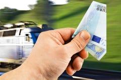 De euro in zijn hand op een achtergrond van trein stock fotografie