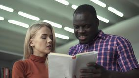 De Europese dame en de Afrikaanse Amerikaanse mens bespreken boek in de bibliotheek stock footage