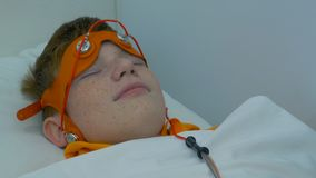 De Europese elektro-encefalografie van het kindgedrag Een procesfragment Rheoencephalography - een arts maakt elektroden vast stock fotografie