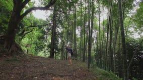 De Europese meisjesreiziger neemt foto op smartphone in de tropische aanplanting van het bosbomenbamboe stock videobeelden