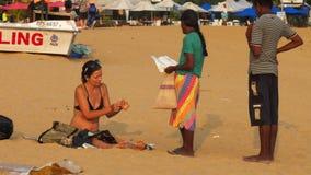 De Europese toerist zit op strand tegenover bruine lokale verkoper stock footage