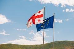 De Europese Unie en de Georgische vlaggen vliegen naast elkaar, op een achtergrondberg en een hemel Stock Fotografie