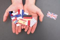 De Europese vlaggen en vlag van Groot-Brittannië op handen Stock Fotografie